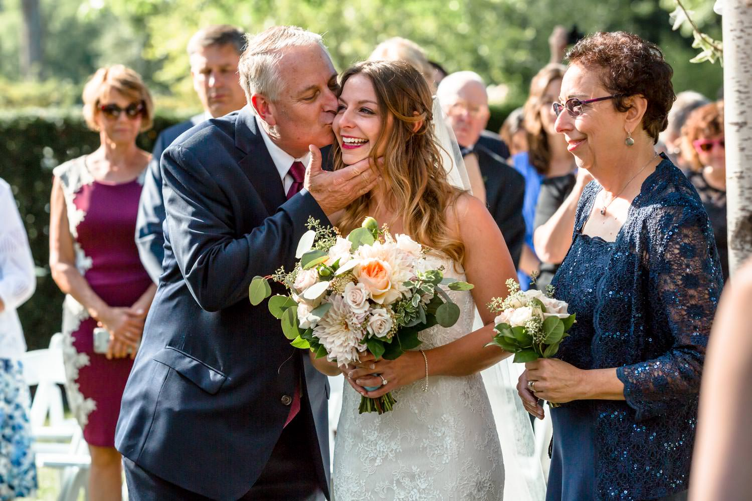 father kisses bride on the cheek as he presents her at a woodstock inn wedding