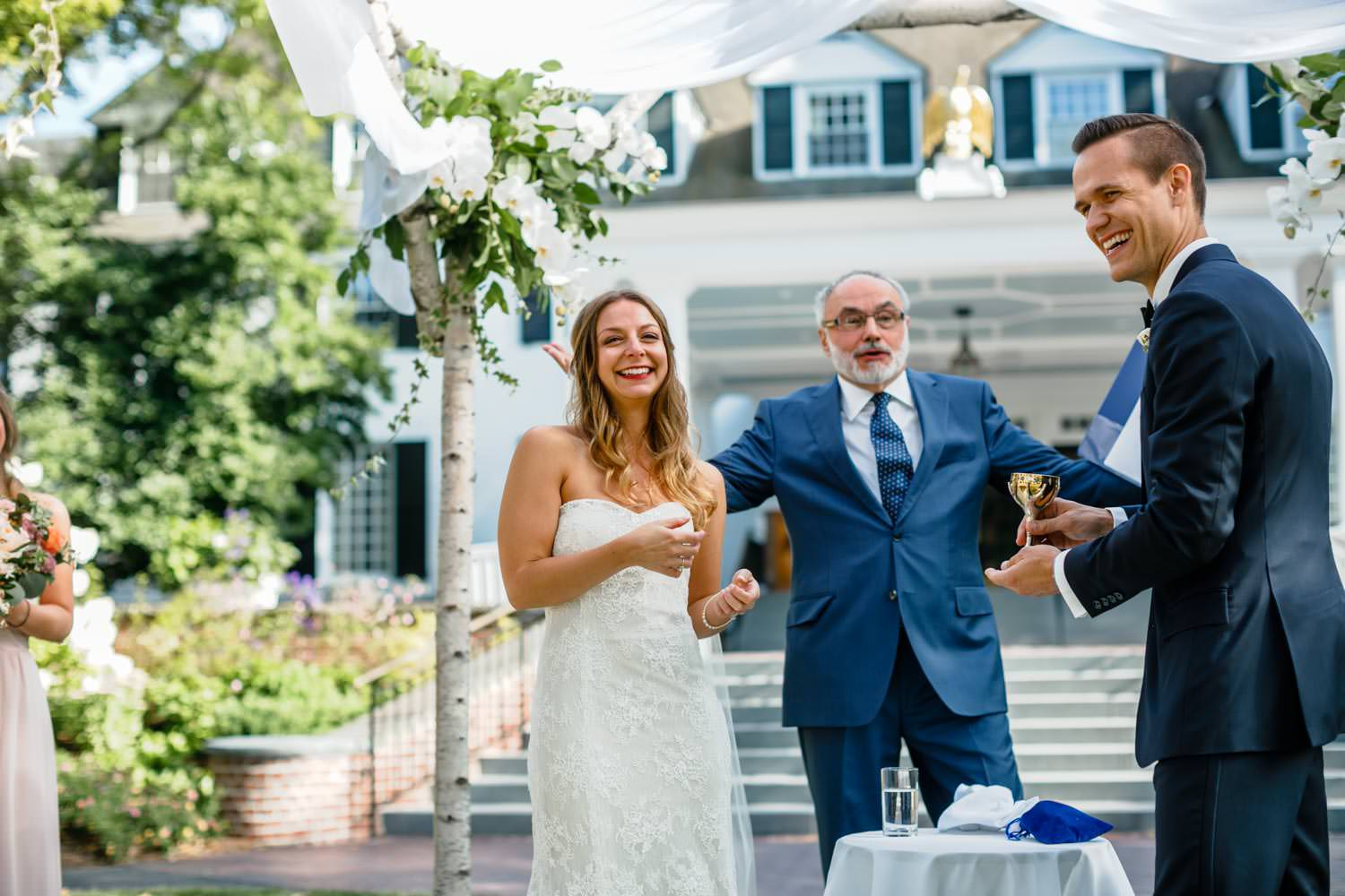 bride and groom laugh with a rabbi under a huppah on the lawn of a woodstock in wedding
