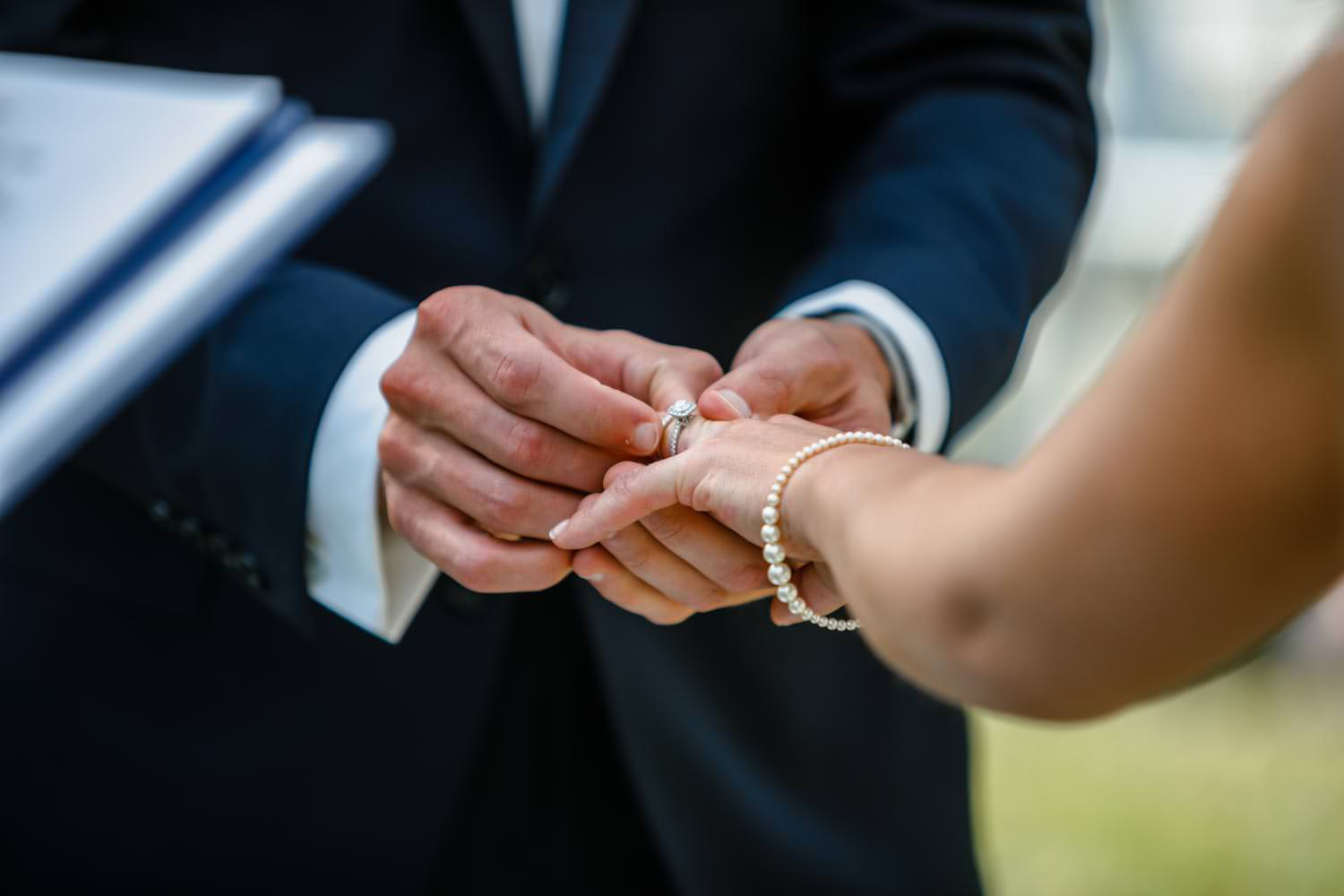 photographer close-up of groom placing ring on brides finger