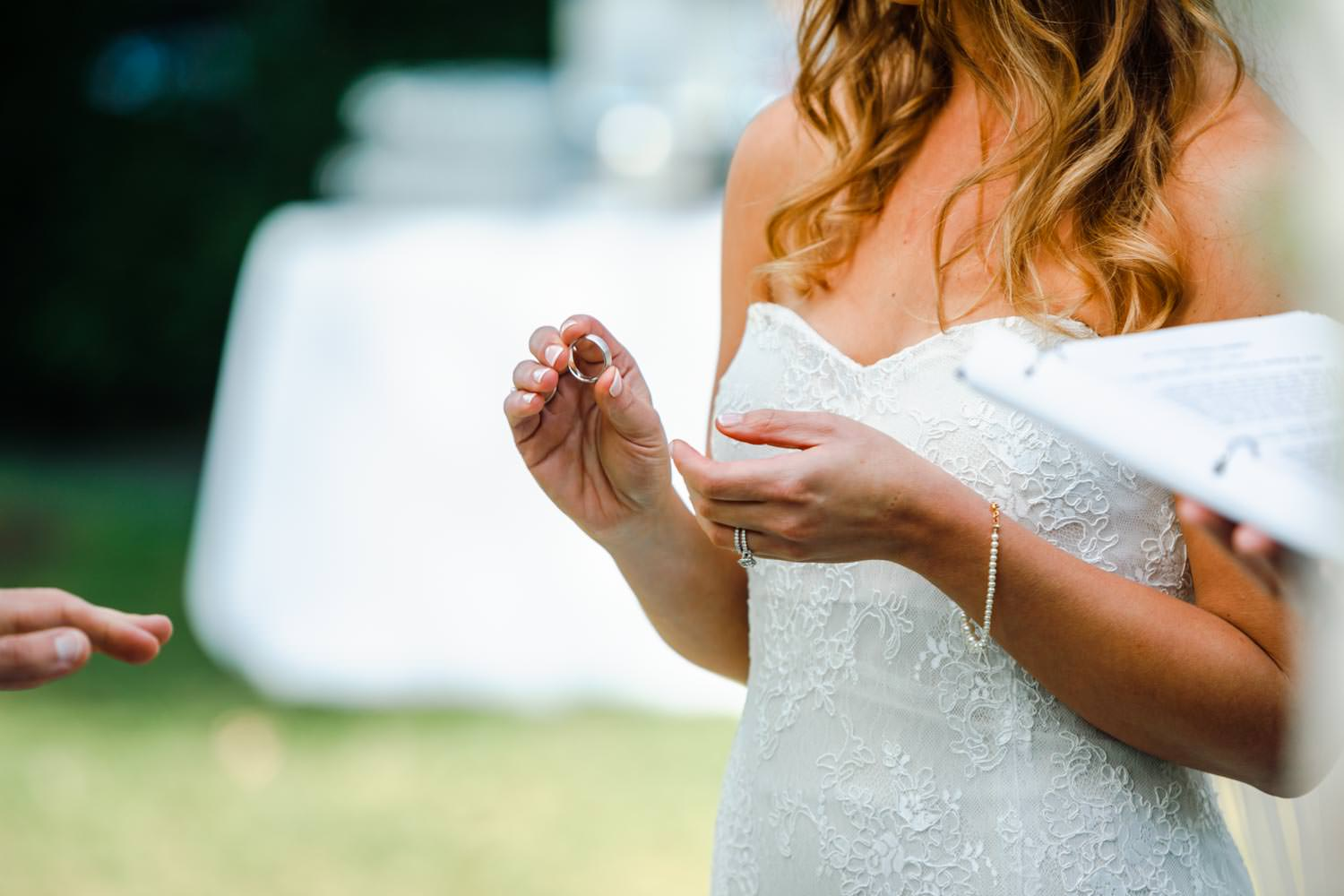 bride holds wedding ring for photographer at woodstock inn wedding in vermont