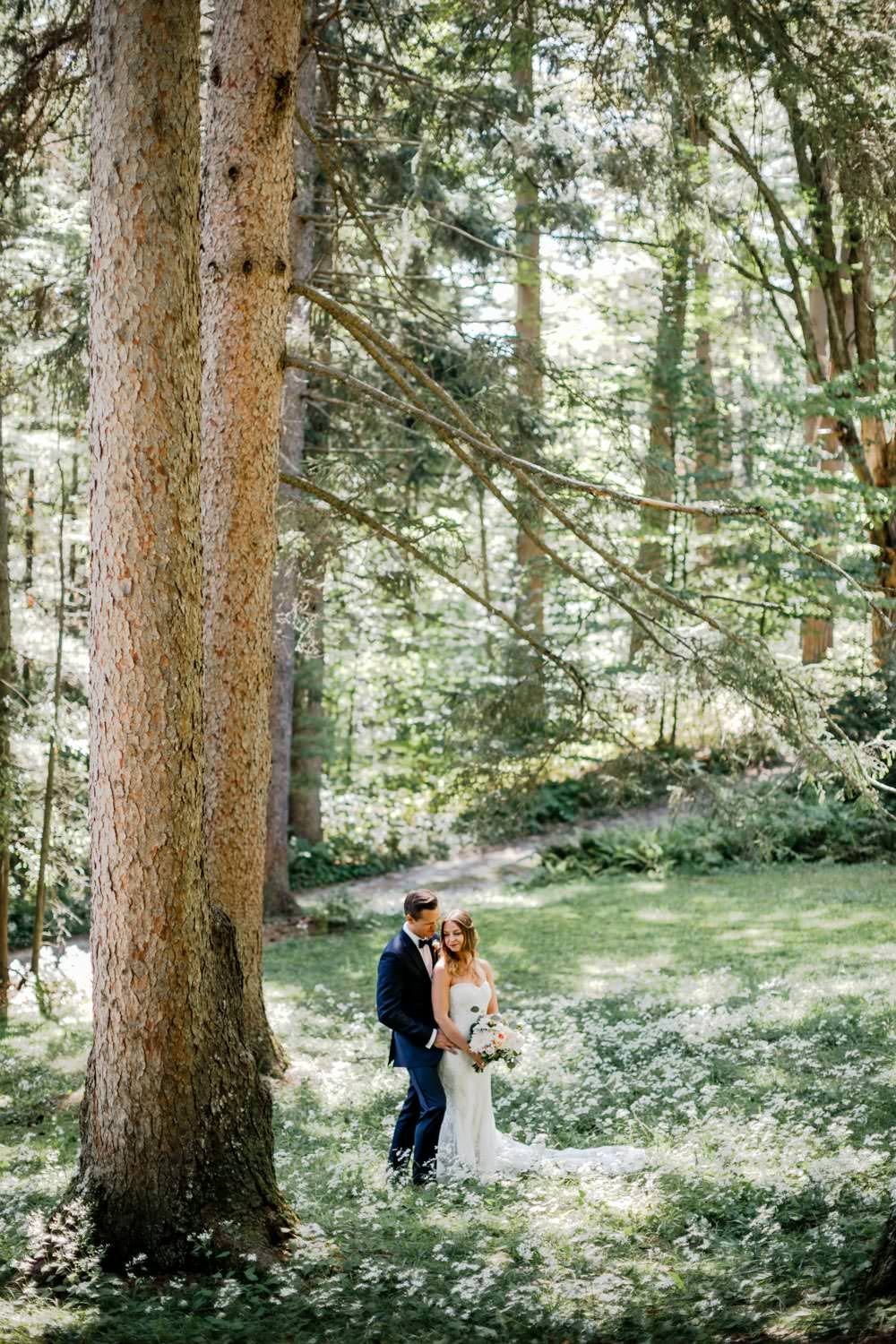 wedding couple stand next to a tree in the woods at the woodstock inn