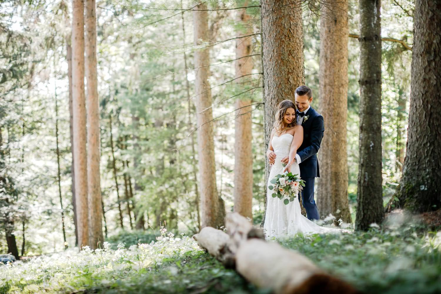 bride and groom embrace next to log in the woodstock inn woods