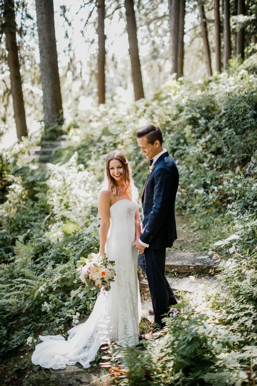 groom holds brides hand as they walk up a path through the woods in woodstock vermont
