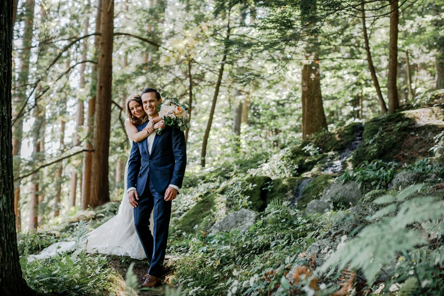 bride and groom look at vermont wedding photographer as they walk through the woods at woodstock inn