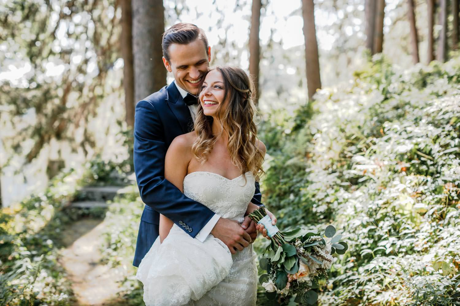 wedding groom holds bride tightly as she gazes off camera with the woods and path in the background