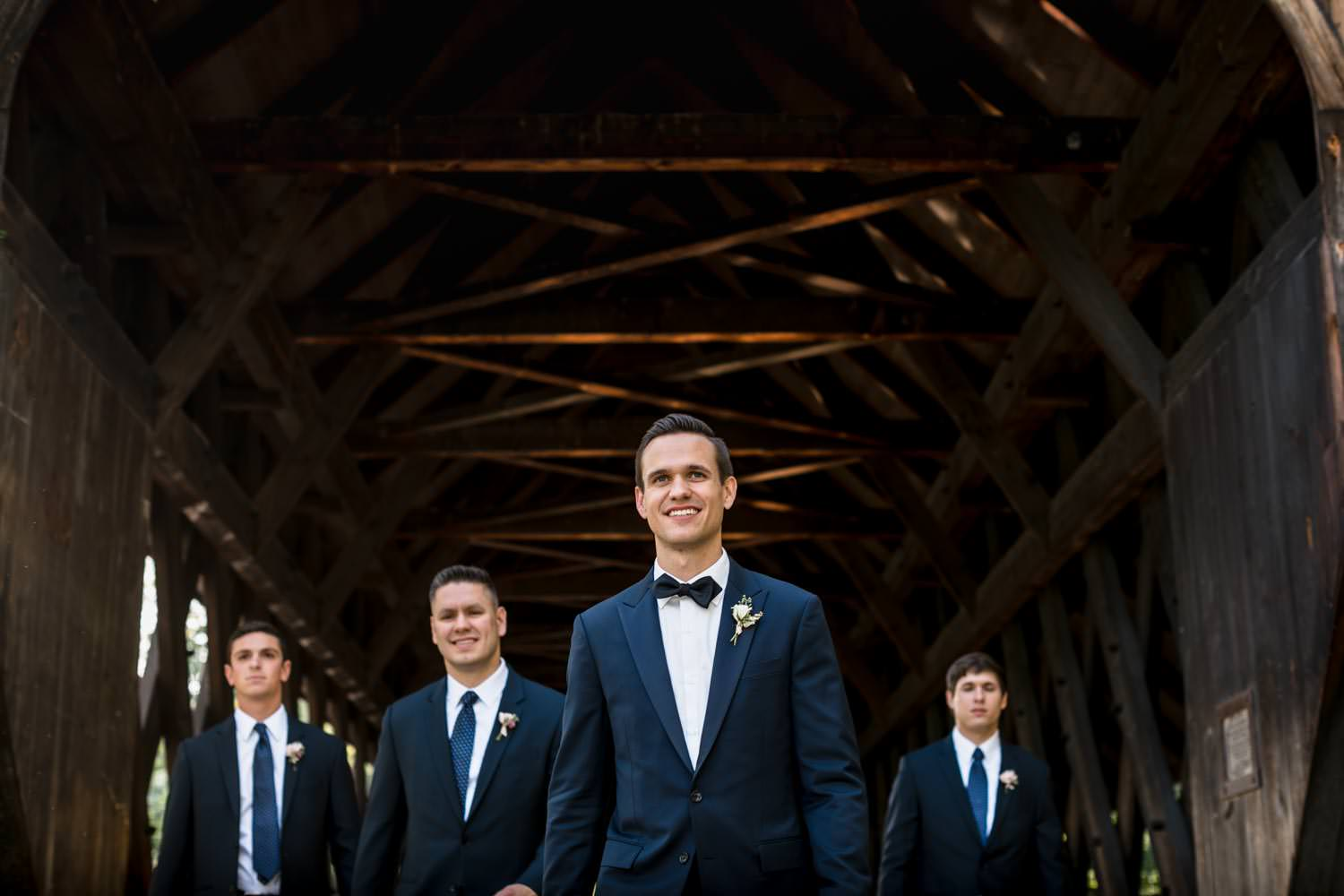 wedding groomsmen walk towards photographer in the covered bridge next to the woodstock inn