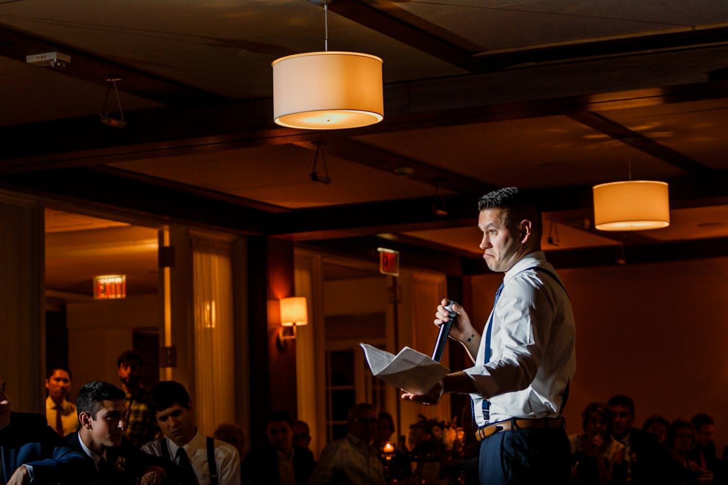 photographer captures funny face of best man giving wedding speech at the woodstock inn vermont