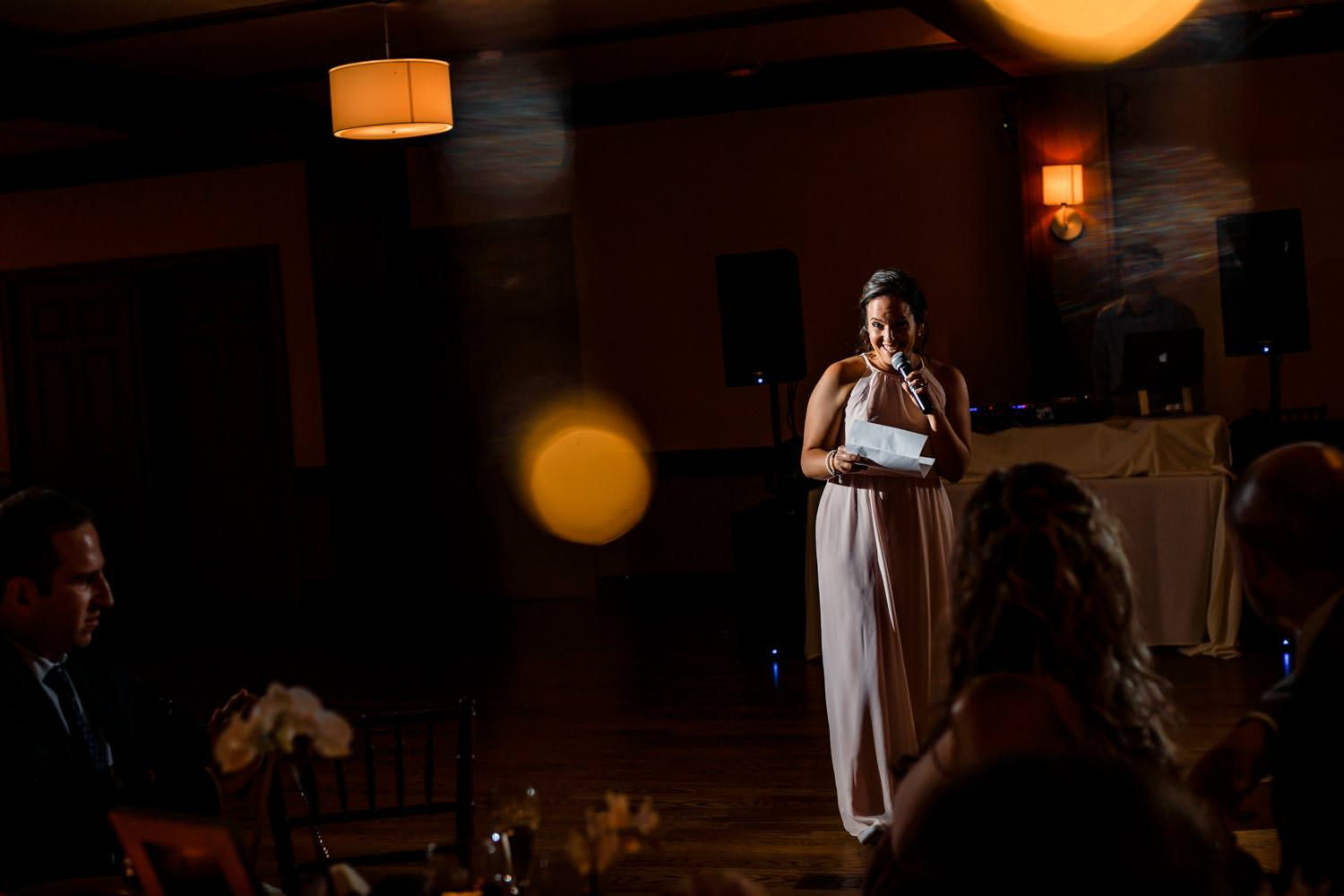 bridesmaid smiles while giving speech during a wedding reception at the woodstock inn