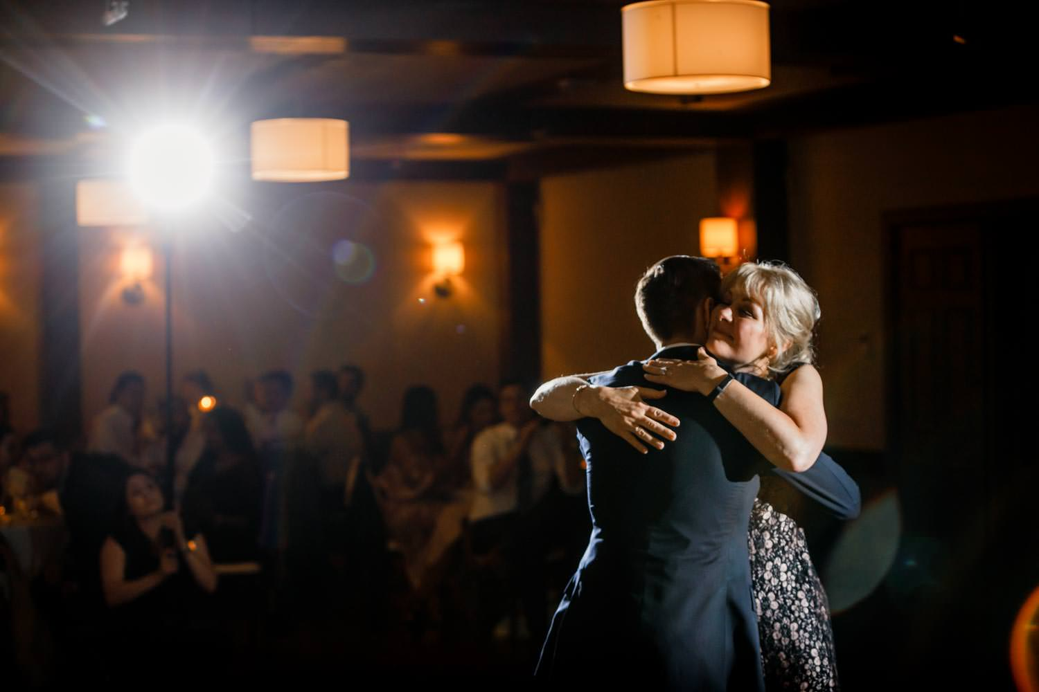 mother hugs groom after formal wedding dance