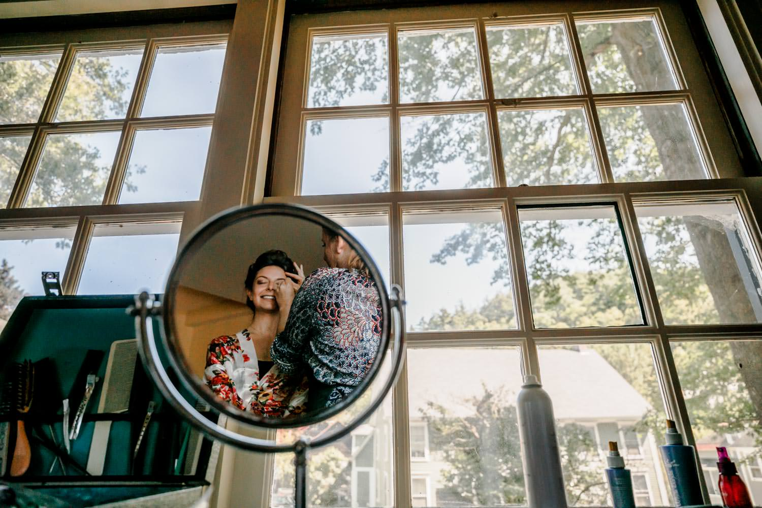 bride getting makeup done in round mirror before her wedding at the woodstock inn vermont