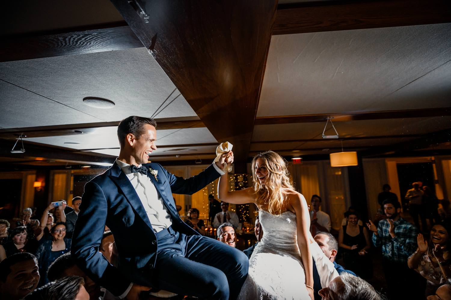 bride and groom on chairs lifted in to the air for wedding dance