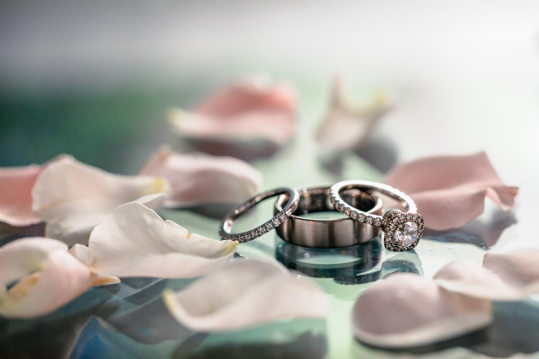 wedding rings set amongst rose petals on reflective surface