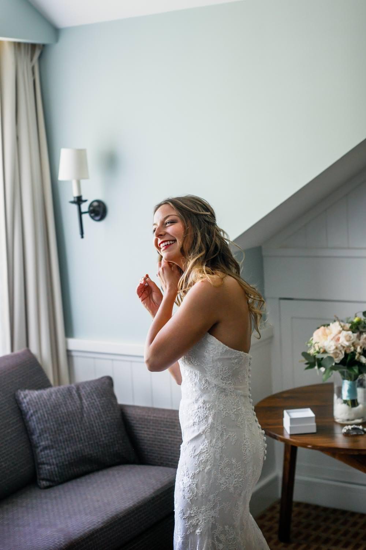 bride puts on earrings in the bridal suite at the woodstock inn