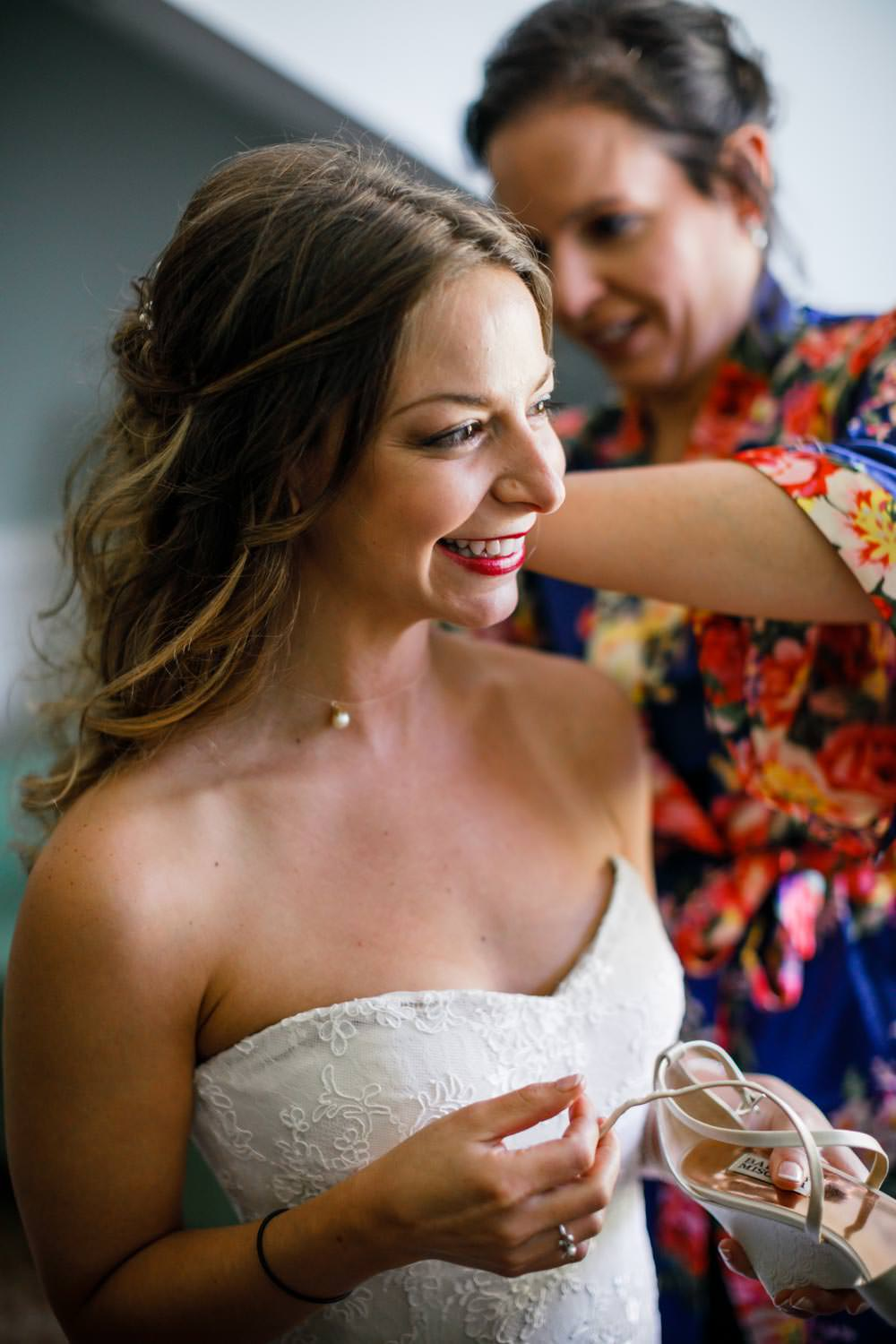 bride smiling away from photographer while getting hair adjusted for woodstock inn wedding