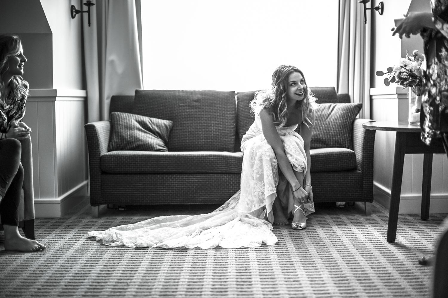 bride puts on heals while sitting on the couch in her suite at the woodstock inn