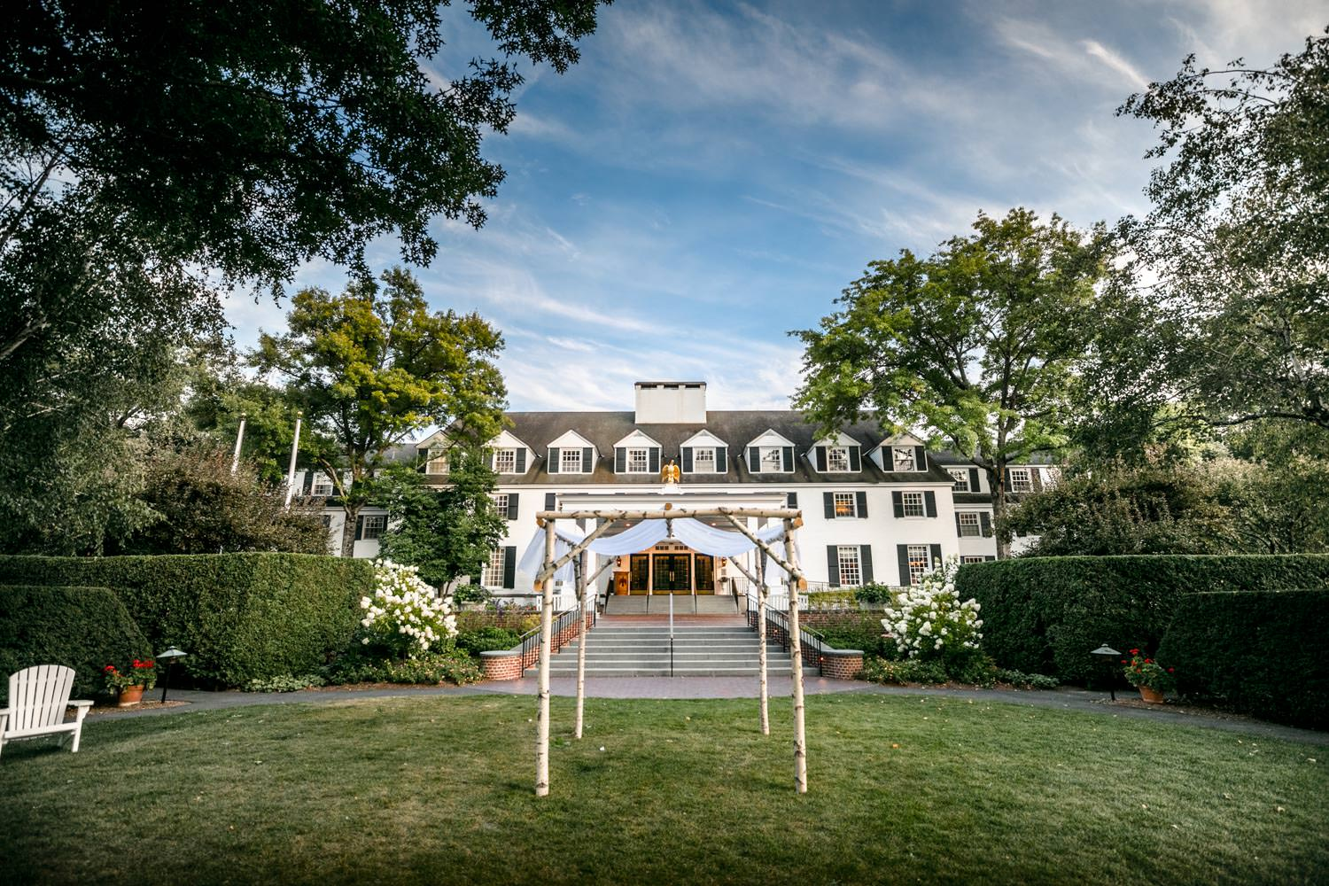 vermont birch wedding huppah with woodstock inn in the background