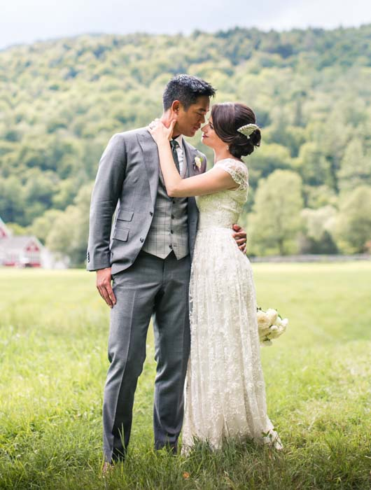 a bride and groom look into each other's eyes in a field